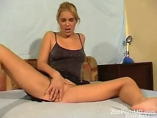 Blond-haired beauty riding a dog's red cock on cam
